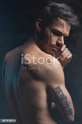 Man with scars on face and back. Halloween theme.