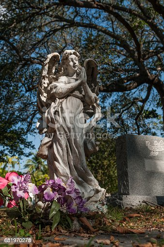 Weathered marble statue of little angel at Miami Cemetery