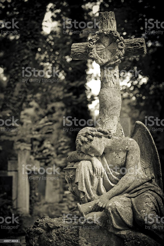 Angel resting under a cross royalty-free stock photo
