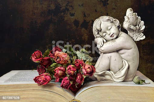 istock Angel, roses and old book on grunge background 627397528