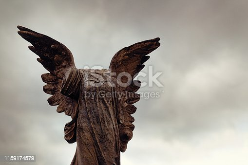 Angel statue looking forlorn with missing body parts. Inscription dates the grave to the 1920s.