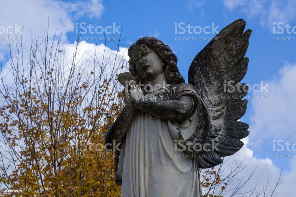 Angel Statue under Fall Foliage and Blue Sky stock photo