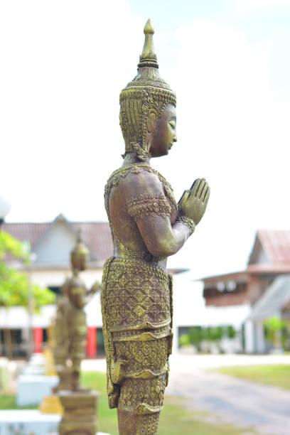 engelsstatue mit thai häuser hintergrund. - buddha figuren kaufen stock-fotos und bilder