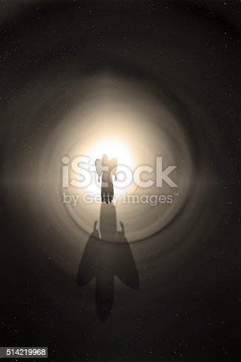 The silhouette of an angel walking toward the light at the end of a tunnel.