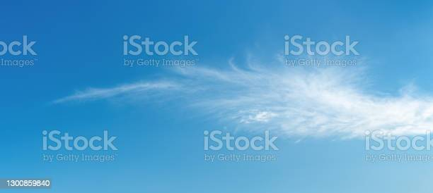 Photo of Angel wing shaped cloud against azure heaven. White cloud like a swan wing high in a blue sky. Translucent cirrus spindrift clouds high up. Purity and serenity concepts. Panoramic skyscape.