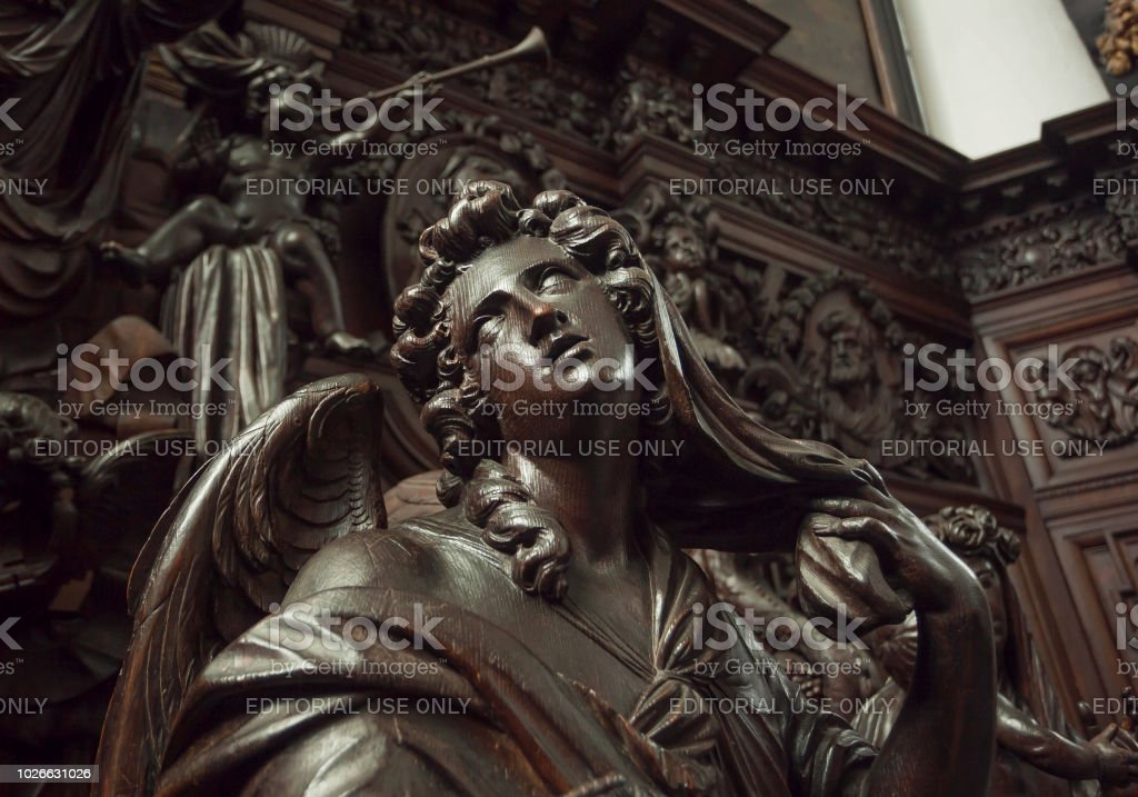 Angel with emotional expression or reflections, wooden statue in 12th century Saint Michael's church stock photo