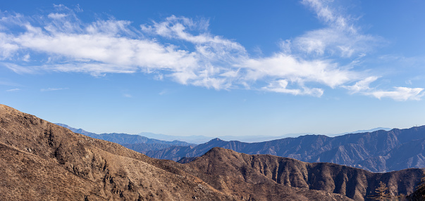 Californian mountain range under blue sky with clouds
