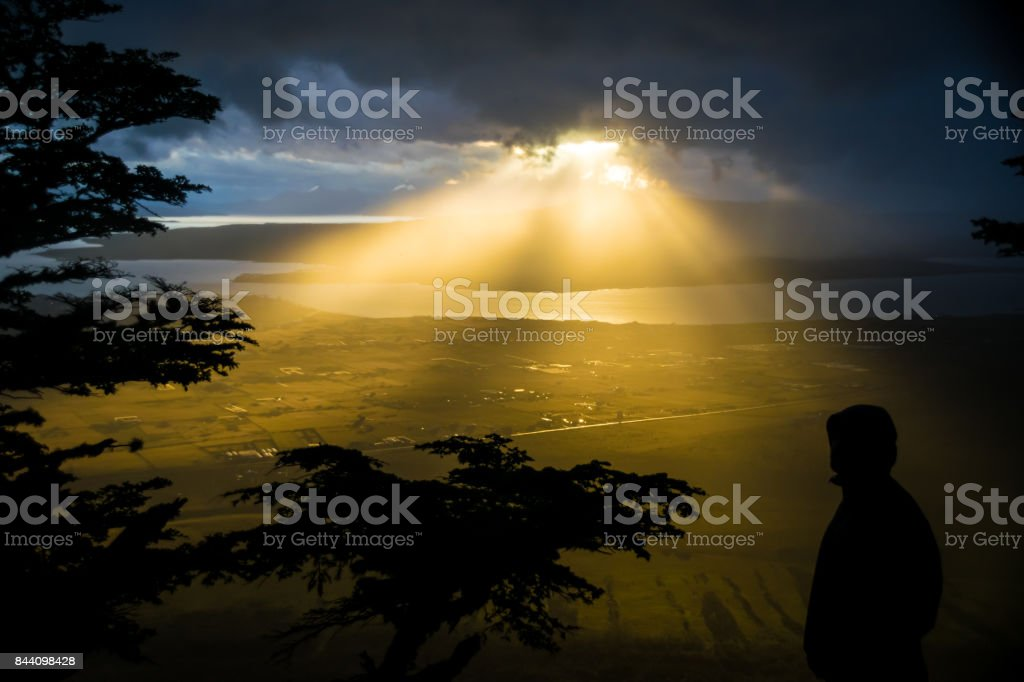 Angels coming down from the sky, a bright ray of light that burstes out from the cloudy sky of Puerto Natales, Chile, South America stock photo