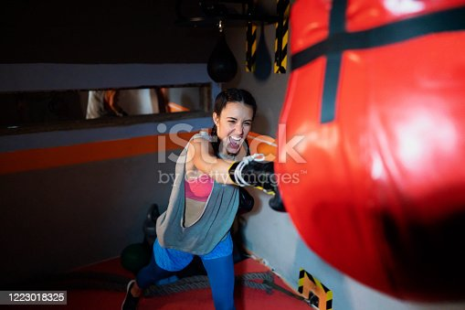 Punching bag workout.   Young female boxer does her training and punches a boxing bag.