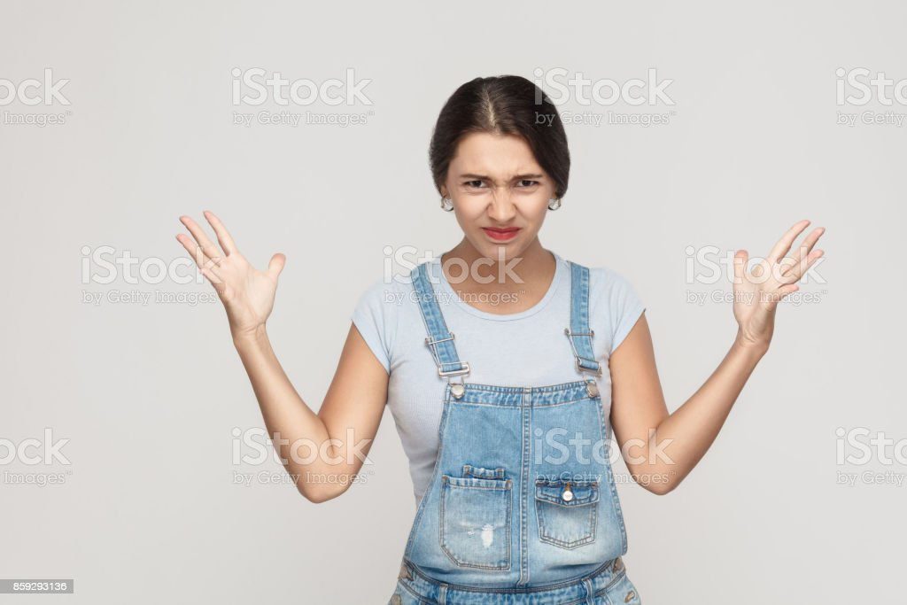 Anger woman in despair and shock. Portrait of young adult angry  woman in blue denimoveralls, looking panic in camera with mouth wide open, with hands up. stock photo