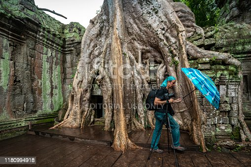 Ta Prohm, Cambodia - September 02, 2019: Appearance from Angkor Ta Prohm Temple of Angkor Thom in Cambodia with photographer and giant tree root under rain with umbrella.