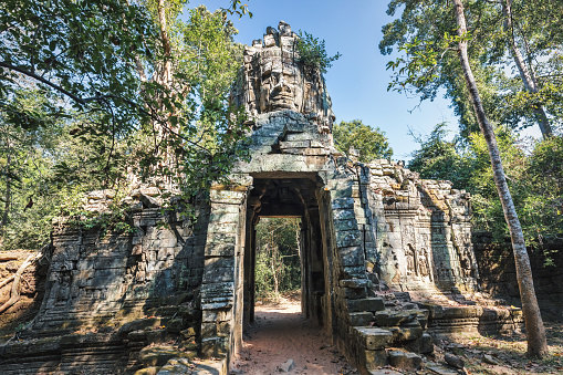 Ancient Stone Entrance Gate with Religious Khmer Face Sculpture on Top of the North Entrance Gate towards the famous Angkor Thom Temple Area. Angkor Thom, Angkor Wat Area, Cambodia, South East Asia.