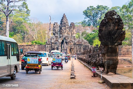 South Gate of Angkor Thom, part of the large temple complex commonly referred to as Angkor Wat close to Siem Reap in Cambodia  People and vehicles are clearly visible on the road entering through the ancient gate