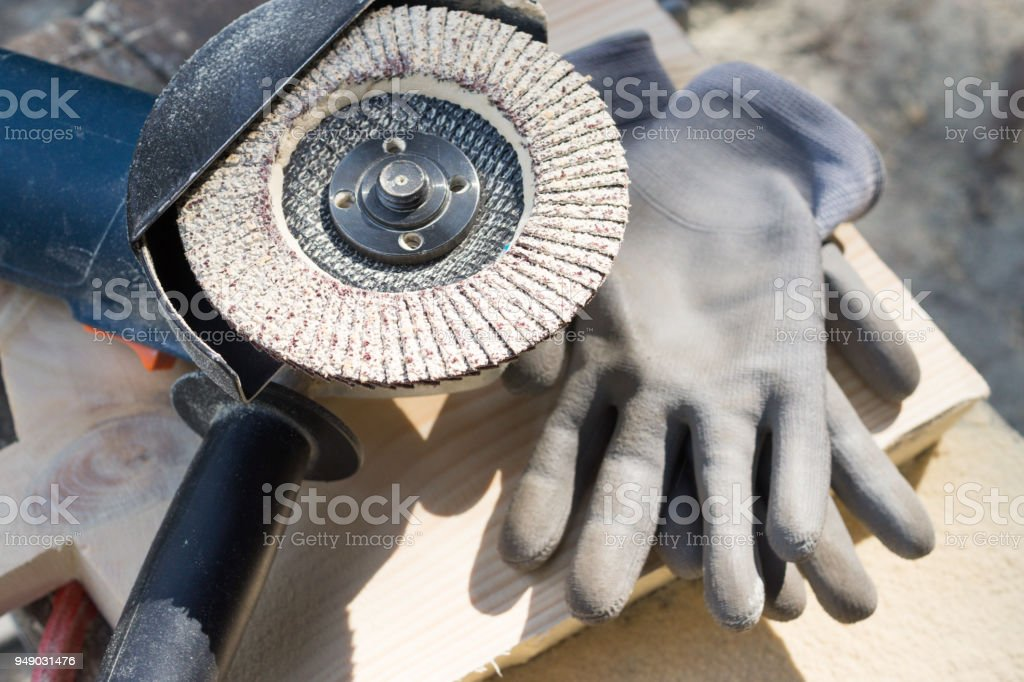 Angle grinder and working gloves stock photo