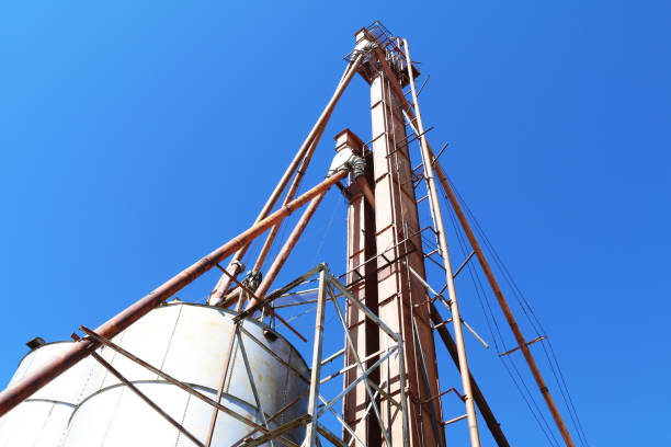 angle view of an agricultural feed grain and corn elevator silo building against a blue sky in rural heartland america perfect for industry farming and commercial agriculture marketing stock photo
