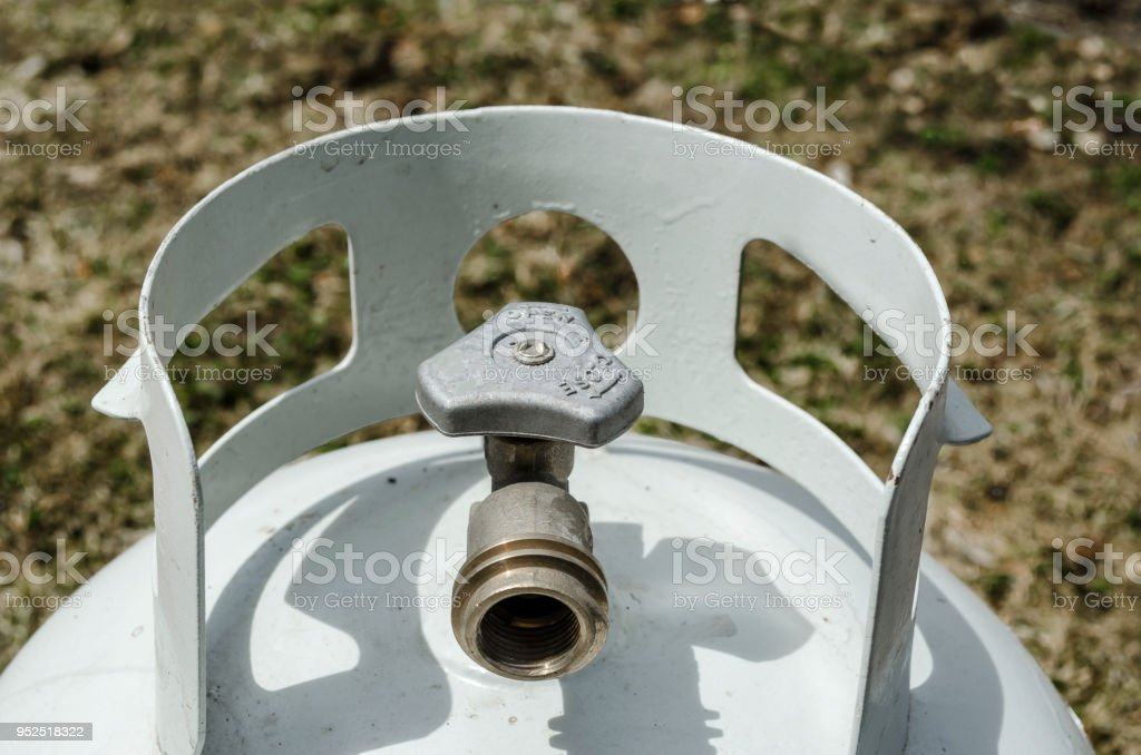 Angled overhead close-up of the top of a white propane tank and brass valve with grass in the background stock photo