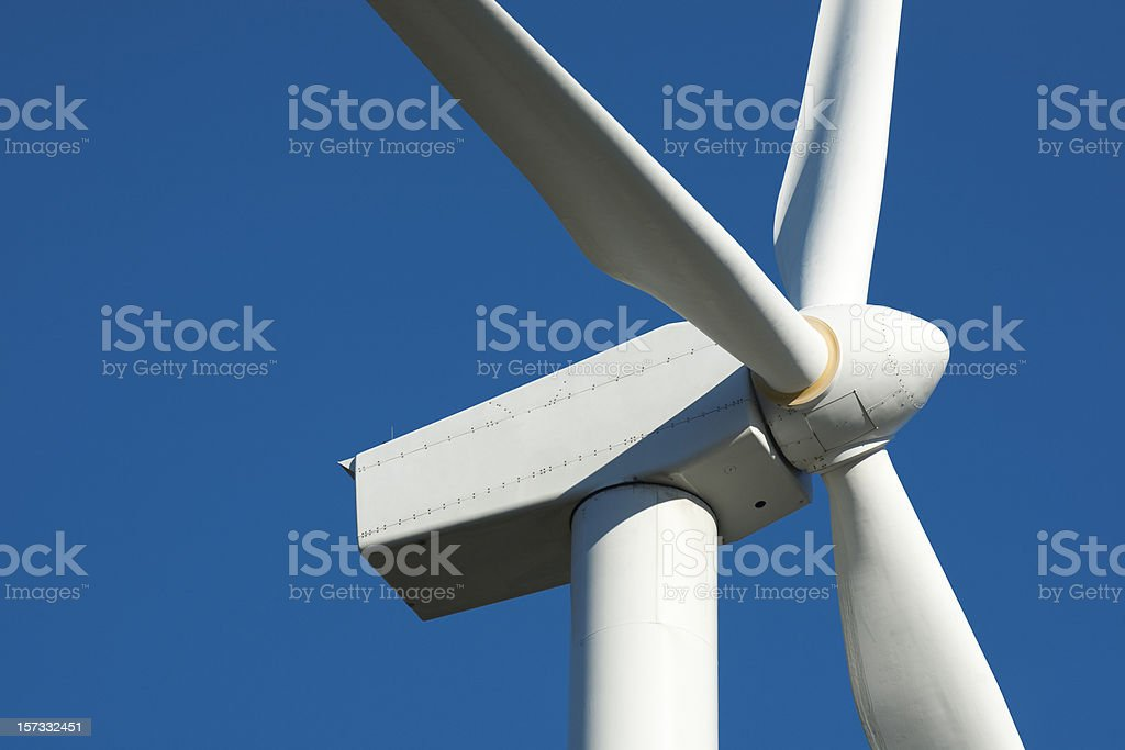 Angled side view of the top of a white wind turbine royalty-free stock photo