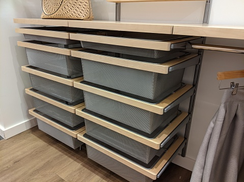 Angled view of a set of wire mesh drawers inside a large walk in closet with wooden floors