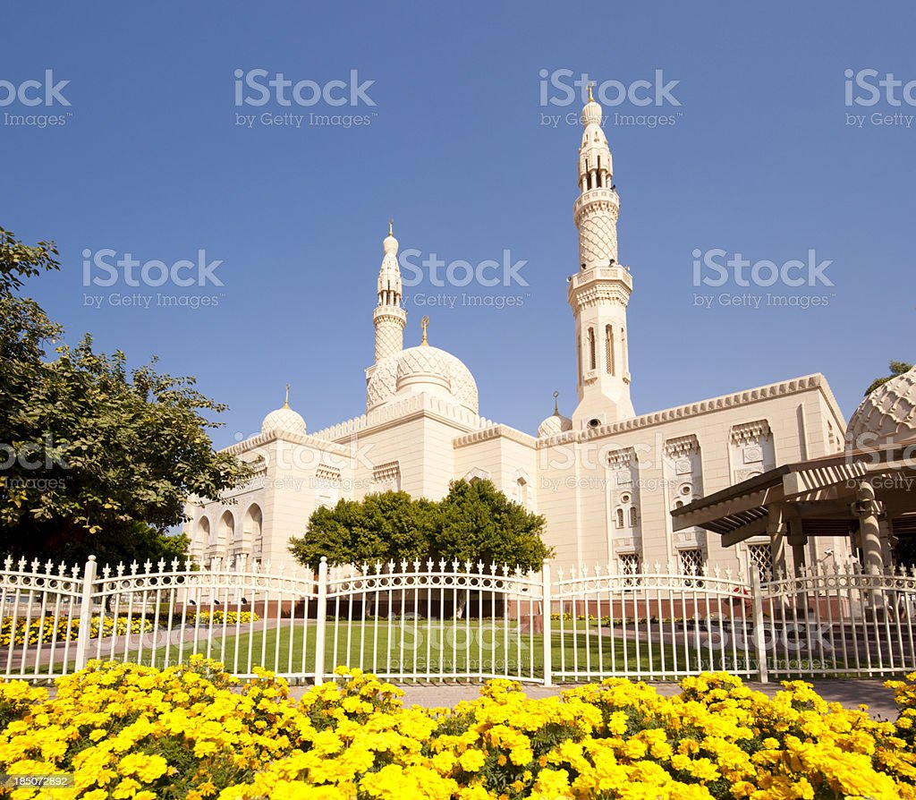 Angled view of Jumeirah Mosque behind fence under blue sky. stock photo