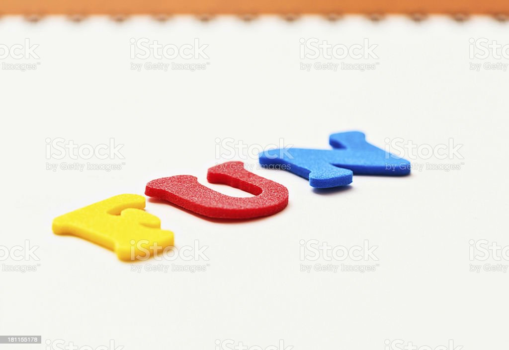Angled view of play alphabet spelling FUN on white background royalty-free stock photo