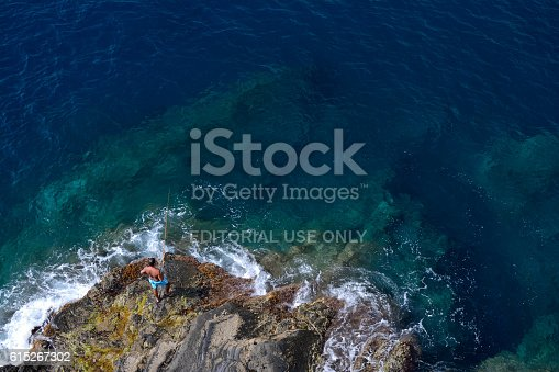 istock Angler catching fish on rock in Manarola. 615267302