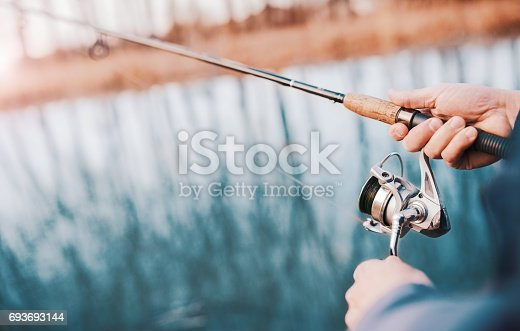 istock Angler enjoys in fishing on the river. Close up photo of fisherman hands. Sport, recreation, lifestyle 693693144