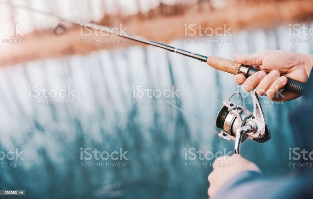 Angler enjoys in fishing on the river. Close up photo of fisherman hands. Sport, recreation, lifestyle stock photo