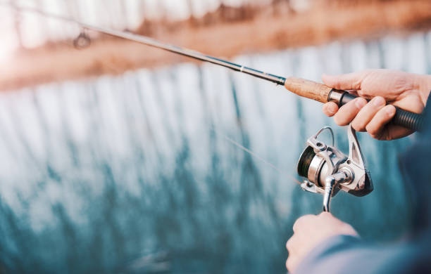 Angler enjoys in fishing on the river. Close up photo of fisherman hands. Sport, recreation, lifestyle Close up photo of fisherman hands. Fisherman angling on the river. Fisherman standing on the riverside and trying to catch a bass. Sport, recreation, lifestyle freshwater fishing stock pictures, royalty-free photos & images