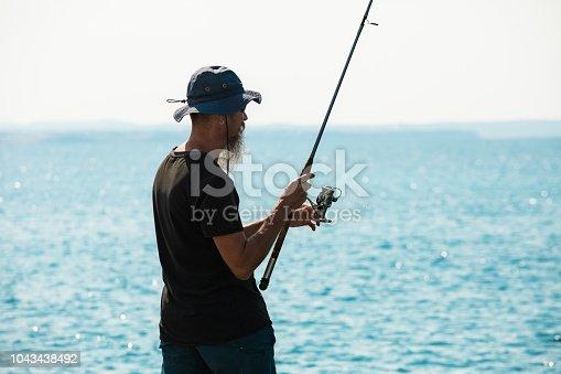 istock Angler fishing at Aegean sea, Greece 1043438492