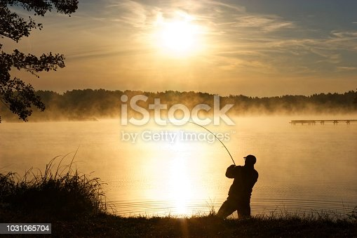 Silhouette of fisherman standing in a lake and catching the fish during foggy sunrise