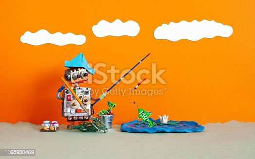 istock Angler robot toy caught big fish. Robotic fishing rest activity concept. Fisherman robotic with accessories rod bucket bait. Summer clouds scape, blue lake on orange sunset background, copy space. 1165930469