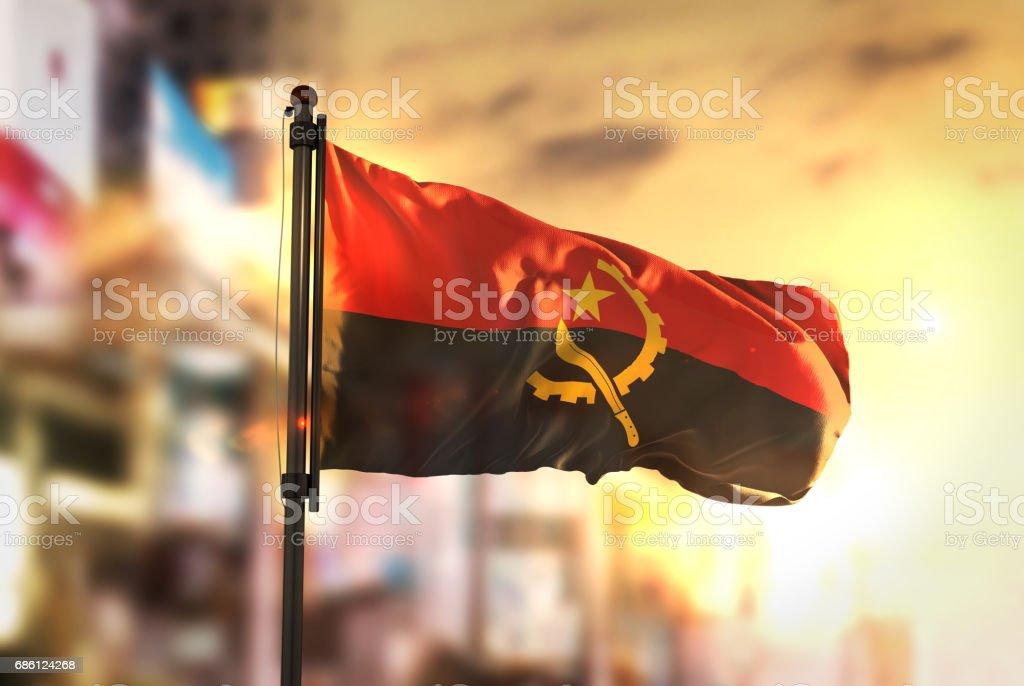 Angola Flag Against City Blurred Background At Sunrise Backlight stock photo