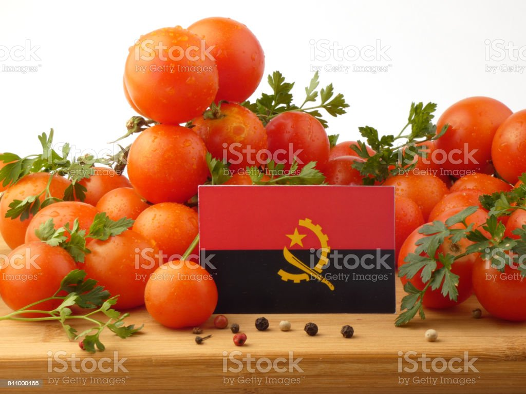 Angolan flag on a wooden panel with tomatoes isolated on a white background stock photo