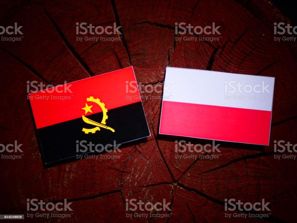 Angolan flag with Polish flag on a tree stump isolated stock photo
