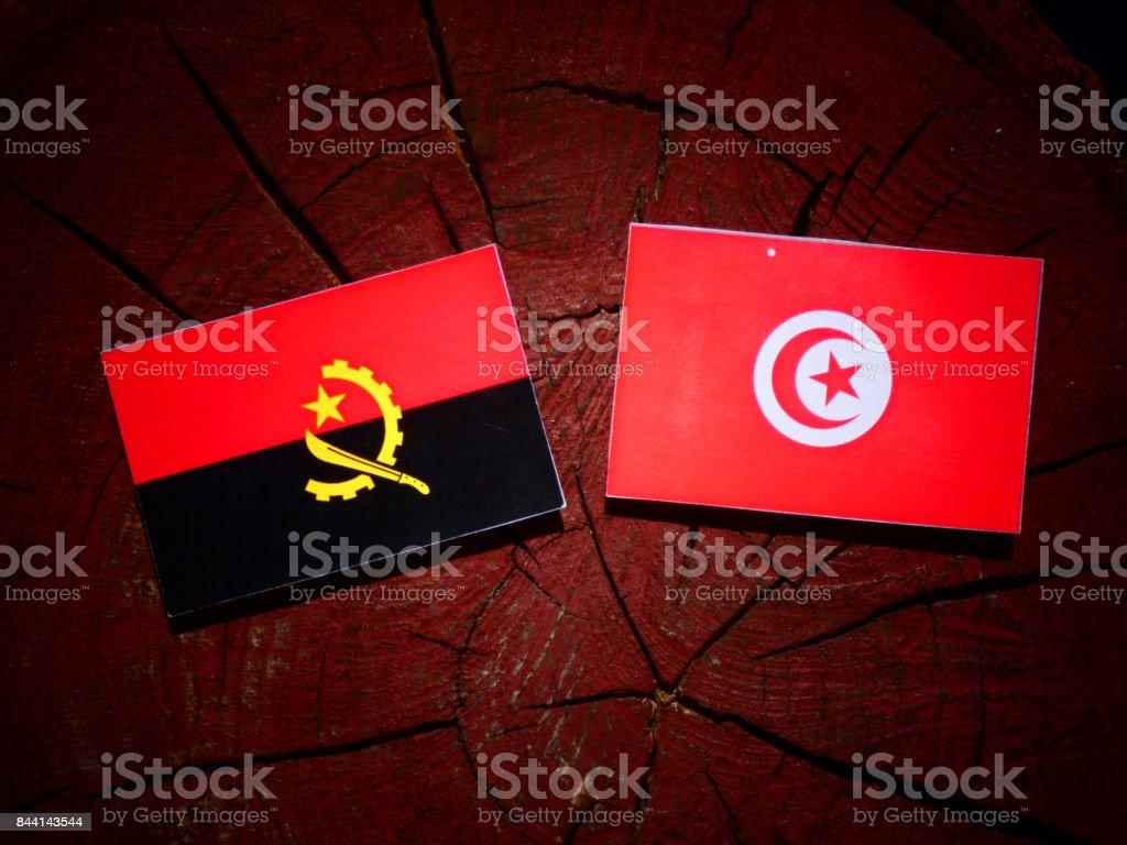Angolan flag with Tunisian flag on a tree stump isolated stock photo