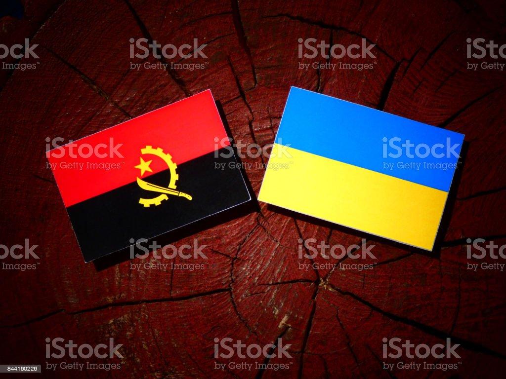 Angolan flag with Ukrainian flag on a tree stump isolated stock photo