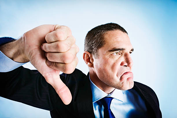 angrily frowning businessman makes thumbs-down signal - thumbs down stock photos and pictures