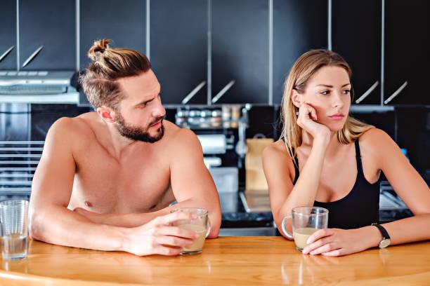 Angru pareja sentada en la cocina pult y sosteniendo café - foto de stock