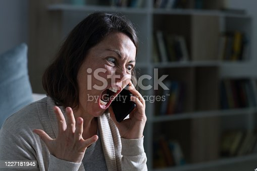 1138361116 istock photo Angry adult woman screaming calling on phone at night at home 1227181945