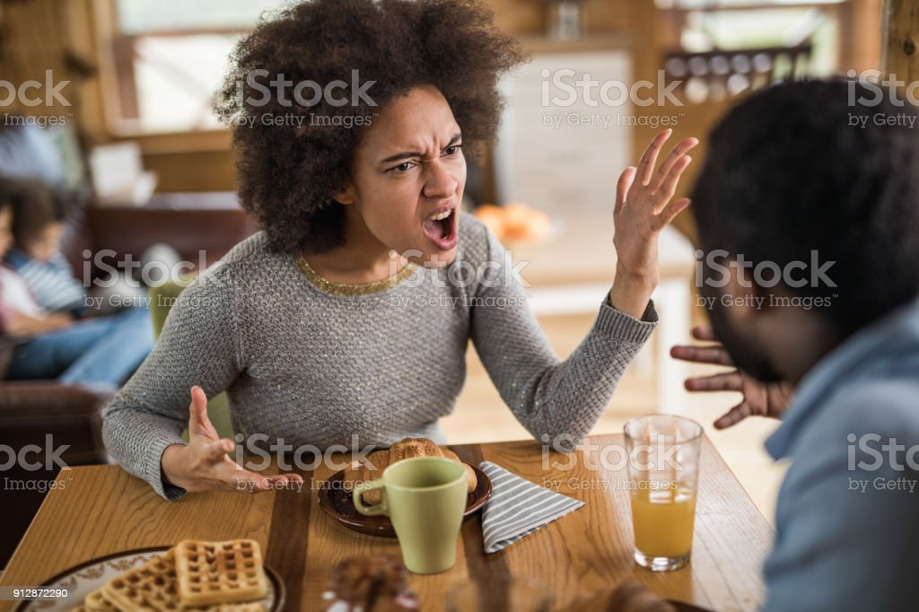 Angry African American woman arguing with her husband at dining table. stock photo