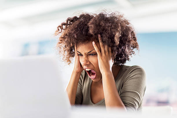 Angry African American woman using computer. stock photo