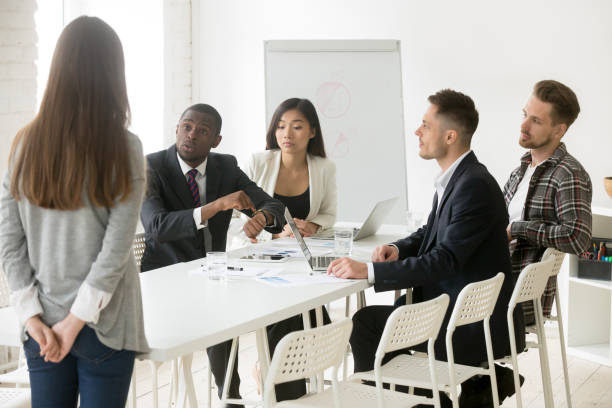 Angry african boss scolding employee for being late at meeting stock photo