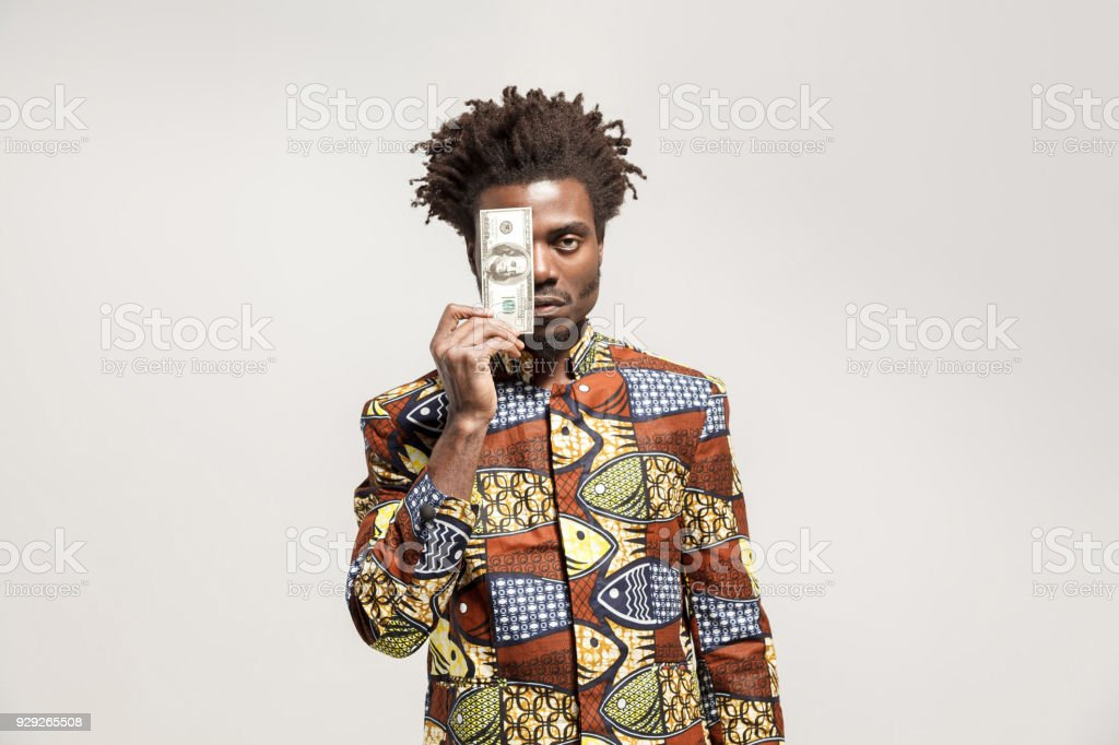 Angry african man holding one dollar stock photo