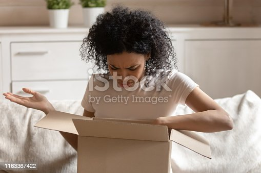 istock Angry african woman unpack carton box feels irritated 1163367422