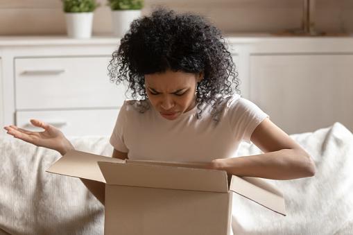 istock Angry african woman unpack carton box feels irritated 1163367422