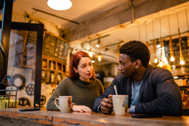 Angry african-american man having a fight at the cafeteria with his jealous girlfriend stock photo