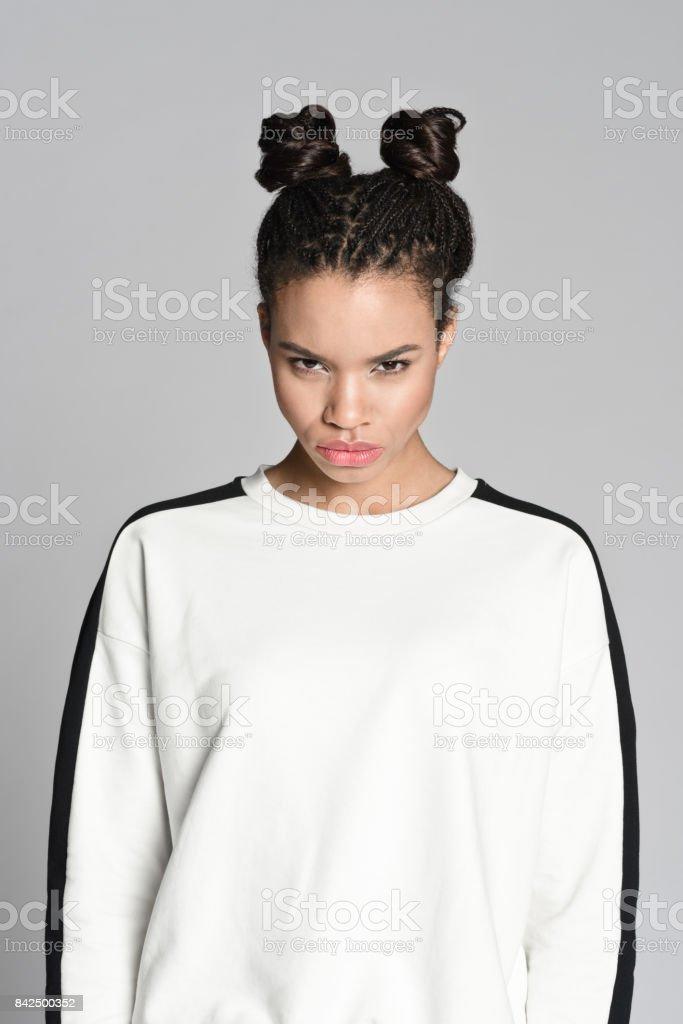 Angry afro american teenager woman Studio portrait of angry afro american teenage woman looking at camera. Studio shot, grey background. 16-17 Years Stock Photo