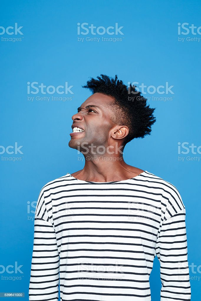 Angry afro american young man Side view of angry afro american guy wearing striped long sleeved t-shirt, clenching his teeth. Studio shot, blue background.  Adult Stock Photo