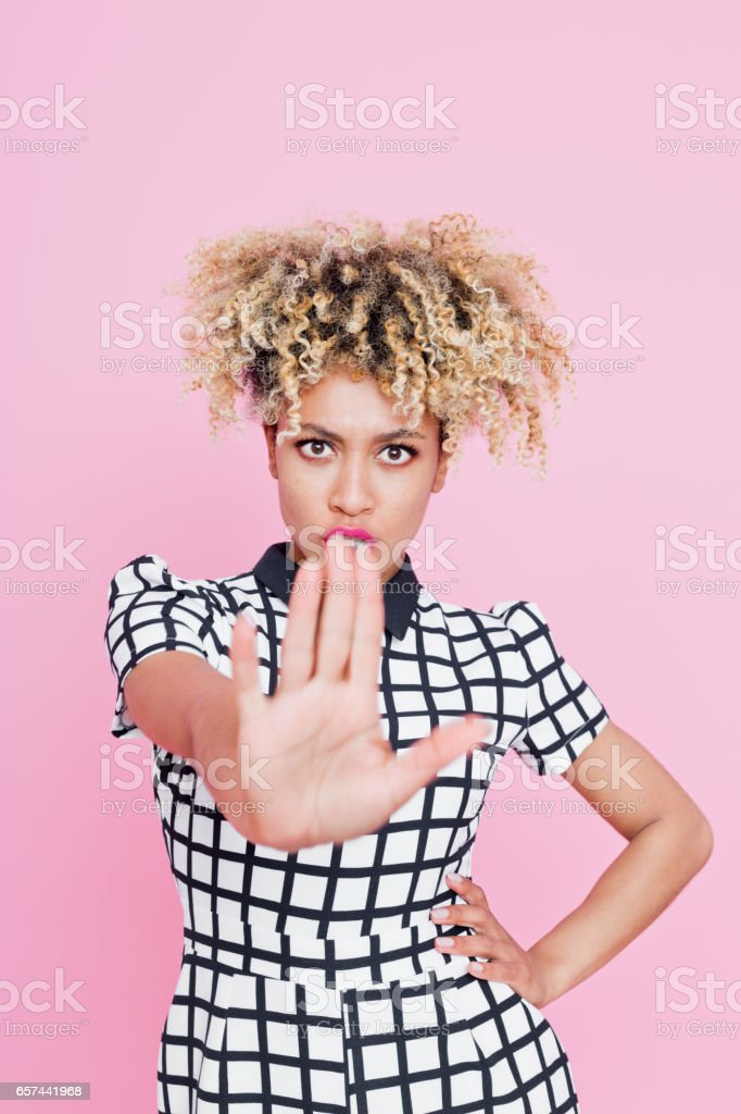 """Angry afro american young woman gesturing """"stop"""" Studio portrait of angry afro american young woman gesturing """"stop"""". Pink background. 20-24 Years Stock Photo"""
