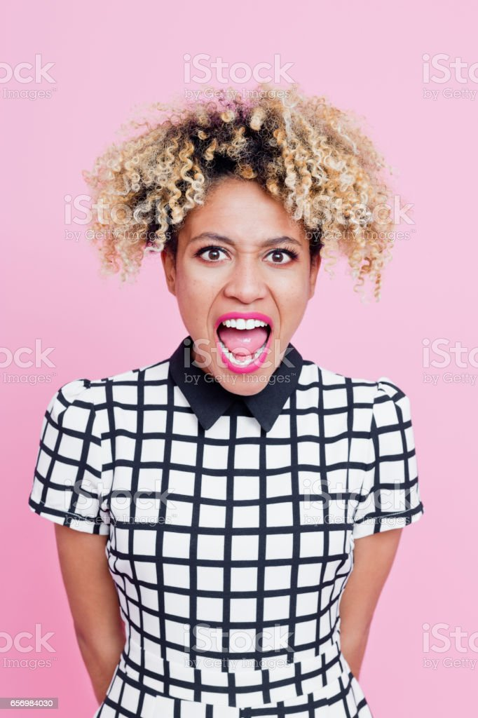 Angry afro american young woman shouting Studio portrait of angry afro american young woman shouting at the camera. Pink background. 20-24 Years Stock Photo